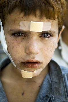 americanphoto:© Lynsey AddarioThe portrait of Khalid, 7, with shrapnel wounds or wounds from an explosion in Kunar Province, Afghanistan, receiving treatment from U.S. army medics.From:It's What I Do: Powerful Lynsey Addario Memoir Excerpt on Censorship