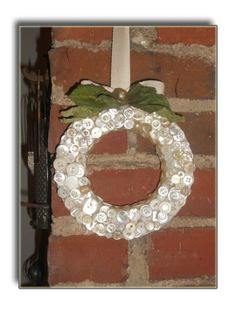 Adorable button wreath hung by a cotton ribbon. So sweet...