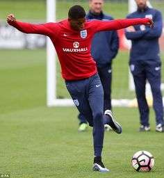 Rashford attempts a 'rabona' while manager Gareth Southgate watches on in Burton