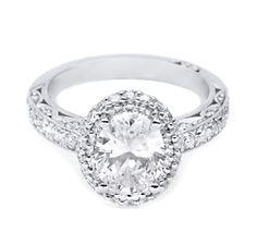 A halo of diamonds makes this oval centerstone bloom on this modern yet classic Engagement ring, featuring an absolutely unique sweet heart carriage that exposes the diamond centerstone, allowing its true beauty to shine.