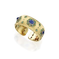 18 Karat Two-Color Gold, Sapphire and Emerald Bangle-Bracelet, Buccellati, Italy The hinged bangle-bracelet decorated with three florets centered by oval-shaped cabochon sapphires, framed and accented by round emeralds