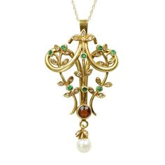 A lovely jewel from the turn of the last century. Bezel set at the base of the pendant is a .67 ct Imperial Topaz. Diamond and Emerald set vines twine up and ar