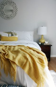 Wood bed frame , yellow throw blanket , white bed set . Pastel yellow , white , beige , grey pillows .