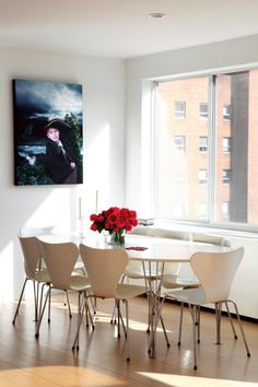 Bold red flowers and unusual art work bring unexpected elements to the simple dining space while natural light from the windows illuminate the table.