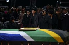 The ex-wife of Nelson Mandela, Winnie Mandela (L), and the widow of Nelson Mandela, Graca Machel (C), stand by the coffin of South African f...