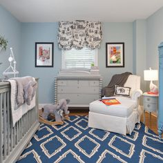 Light blue walls are a classic touch to this baby boy's nursery. A blue patterned rug grounds the space, which also features a gray crib, a gray changing table and an adorable elephant theme.
