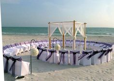 Florida Beach Wedding style from Suncoast Weddings - Check out one of our newest looks! Seashell-inspired SPIRAL AISLE surrounds our four-post bamboo arch, which features a canopy draping and floral tiebacks. The floral tiebacks coordinate perfectly with white and ivory kissing balls at the opening of the aisle!