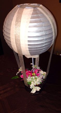 DIY Hot air balloon centerpieces. can use lit paper lantern and basket of flowers.  So cute!