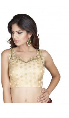 A Benarasi gold sleeveless saree blouse patterns  with cutwork leaf shaped neckline Concealed in - built cups Side zip closure Complete back highlighted with gold cut pipe Accentuated with tassel hangings Can be complimented both your  ethnic and contemporary saree's  Recommended for all petite to medium sized women. For more detail visit http://www.kbshonline.com/