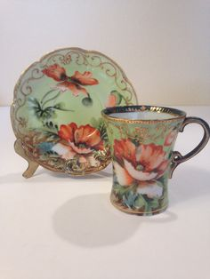 Antique Porcelain Hot Chocolate cup set. It is decorated with a stunning hand painted poppy design, and detailed gold scroll trim.