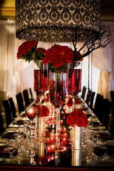 Table setting for a red, black, and white wedding with roses and damask print.