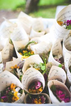 Blooms in paper sheet music cones - a beautiful way to give guests flowers to throw at the happy couple!