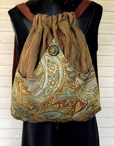 Original handmade backpack made with a brown upholstery strie. The outside pocket of this brown and seafoam green tapestry fabric arches in the