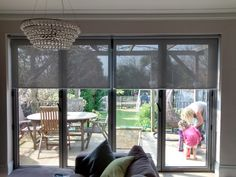 Sunscreen roller blinds over bi-fold doors in living room. Supplied and installed by The Blind Shop.