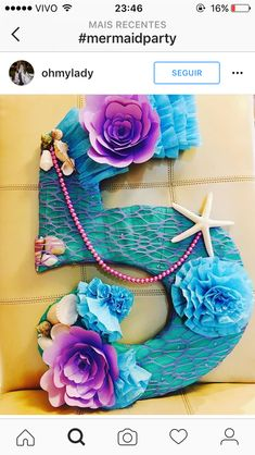 Love the colors!!!  Maybe pink flowers instead of purple, although the purple and blue make an awesome combo.  Love the shells and beads too.