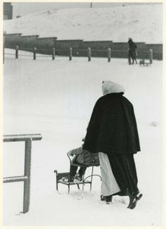 Boulevard in winterstemming, ter hoogte van Paviljoen von Wied; op de voorgrond een Scheveningse vrouw in dracht met een sleetje. 1962 Fotoburo Meyer #ZuidHolland #Scheveningen