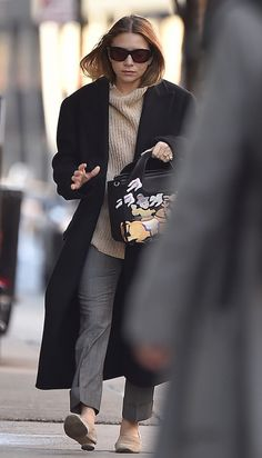Ashley Olsen wears sunglasses, a ribbed sweater, long coat, embroidered bag from The Row, cropped grey pants and flats
