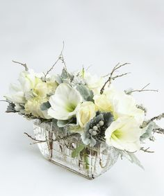 Frosted Whites A pristine collection of white amaryllis and white roses is accented with simple seasonal textures. Designed in a beautiful rectangular glass vase, this arrangement is sure to bring the look of luxury this holiday season.
