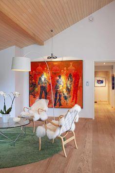 """Håkon Blekens maleri bærer navnet """"Skandale i selskapslivet"""". Det fargesterke innslaget skaper varme mot hvite vegger og utgjør en effektiv kontrast både i form og farge til det blekgrønne salongteppet."""