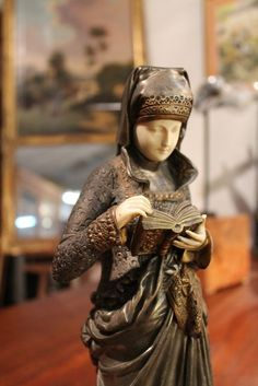 Chryselephantine bronze statue depicting a woman reading, wearing a richly carved medieval dress. Hands and face carved ivory. 41cm height. A.Carrier.Belleuse signed on the terrace. On the base plate bearing the annotation: Woman Reading by Carrier Belleuse