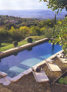Hillside limestone pool with view of countryside.