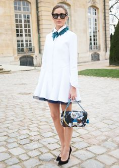 Olivia Palermo in a white dress with collar, piece of statement jewelry, and black heels