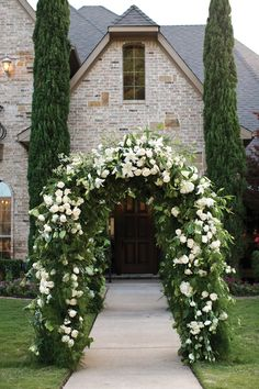 This floral arch entrance is just beautiful. Photo by Jason Kindig. #texaswedding #weddingflowers #floralarch