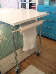 Clever rolling table for craft room/office/guest bedroom.  This room is brimming with clever storage and functionality ideas.