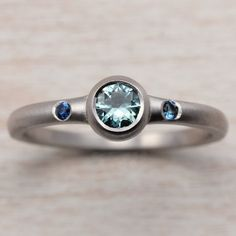 A customized engagement ring with a fair trade light green Montana sapphire center stone and Australian sapphires side stones, set in palladium with a matte finish.
