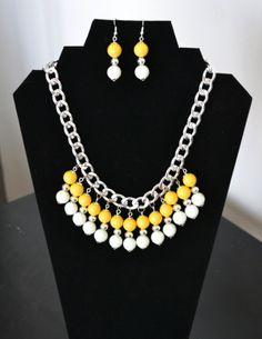 Collar de perlas de cristal en blanco y amarillo, y perlas de metal.