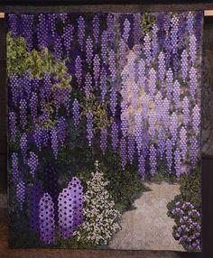 Blauwe-Regen (Wisteria) by Anna Maria Schipper-Vermeiren. Made with mini hexagons appliqued onto snail's trail blocks