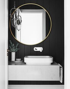 A monochrome bathroom with a round mirror.