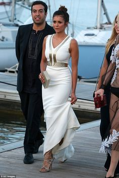 Looking all-white! Nina Dobrev was an elegant vision in figure-hugging white dress with a metallic trim as she arrived on the deck at a port in St. Tropez on Wednesday, ahead of Leonardo DiCaprio's Foundation Gala