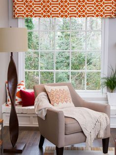 AFTER: Some white paint and a few decorative pillows turn the formerly red bricks into nice, bright window seats. Orange accents like the window valances add a pop of color to the neutral walls and furniture.