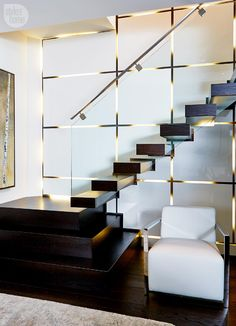 Staircase leading down into the basement - the panel opaque glass wall with brass inlay and back lit; stairs and glass railing nice too