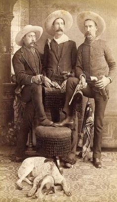 "These 1885-1895 armed Arizona cowboys have a total of six pistols, three of which are 7.5 inch barreled Colt Single Action Army ""Peacemakers"". The man to the right of the image has an ivory-gripped Colt in a ""Cheyenne"" style tooled double-loop holster. The center man has a double holster rig, and one of his smaller pistols is a ""Bulldog."""