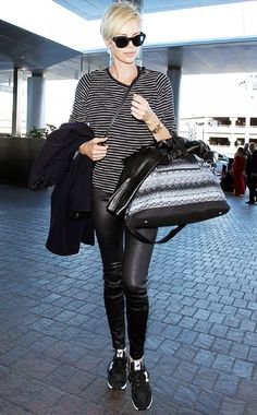 Charlize Theron wears a striped top, leather pants, sneakers, black sunglasses, and a printed carry-on bag