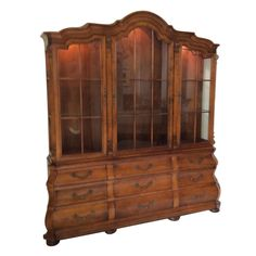 This most beautiful display cabinet! Made of pecan wood. It contains 3 separately enclosed upper cabinets with glass shelves. Each cabinet is lighted separately to illuminate some of your most cherished pieces. The lower half contains 9 drawers which can be used to store silver, tablecloths, etc.  The lower center drawer has a Silver drawer, built in with a velvet bottom and cover top that protects silverware from the elements and tarnishThis item is in perfect shape, with no known…