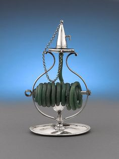 This exceptional and  rare George III-period silver wax jack was crafted by English silversmith John Emes. Boasting a practical yet elegant design, this ingenious item is shaped like a candlestick, with a loop handle and thumb plate, but instead feeds a coil of wax up to be easily lit and melted. The conical candle snuffer, conveniently attached with a chain, extinguishes the flame when the jack is not in use. Hallmarked London, 1807
