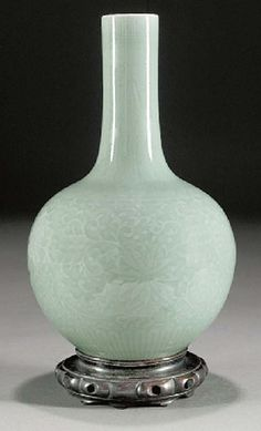 A Chinese pale celadon glazed bottle vase, 19th century, underglaze blue Qianlong seal mark  carved with scrolling lotus sprays beneath a band of stiff leaves to the neck -- 13in. (33cms) high, wood stand.