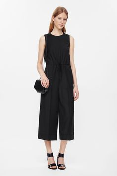 This wide-leg jumpsuit is made from lightweight wool with a soft finish. A loose fit and a drawstring waist, it has a dropped crotch, neat pressfolds, hidden back zip and wide fold ups.