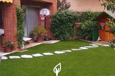 Césped artificial en el jardín de tu casa adornado con un camino de piedras.