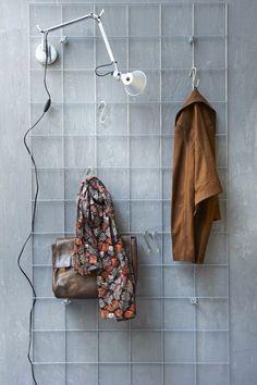 In plaats van klimop, hangen er jassen en tassen aan deze gaasmat. De gaasmat is verkrijgbaar op de tuinafdeling van de goedgesorteerde bouwmarkt, bijvoorbeeld bij Praxis. Het gaas is met vleugelmoeren bevestigd. Vtwonen.
