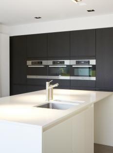 Lage keukenopstelling wit, hoge kastenwand in een (donker) houtpatroon.
