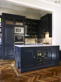 I adore this efficient, compact set-up with the navy cabinetry and stunning herringbone floors...