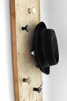 En gammel planke har fått påmontert vakre knotter og er dermed egnet for oppheng av hatter, smykker eller klær.