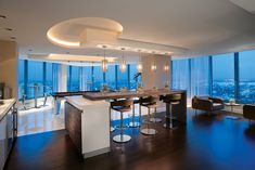 A Home In The Sky Miami Penthouse Palm Beach - The game room and bar area on the third floor serves as an entertainment space. Linen-textured acrylic pendants descend over a bar that seats up to eight on Allermuir barstools.