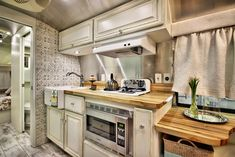 Interior living space of our custom-designed shabby chic 1967 Overlander Airstream trailer. Adding an accent of color with a mint green SMEG refrigerator paired with rigid butcher block countertops and an oversized farm sink - a dream home-away-from-home kitchen!