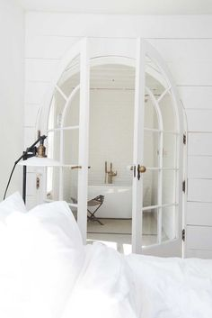 White ensuite bathroom behind glass doors in the beautiful farmhouse of interior designer Leanne Ford.