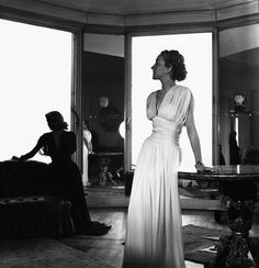 Paris 1946    A woman models a sheer white Edward Molyneux design while another model reclines in the shadows with a black Jeanne Lanvin dress.